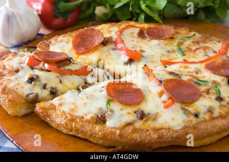 Un bain & mozzarella pepperoni Pizza présenté avec des produits frais sur un plateau en bois Banque D'Images