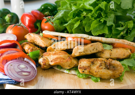 Une douce chaude Chicken shish kebab servi sur un plateau en bois dans un pain pita avec de la salade Banque D'Images
