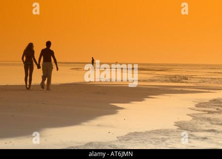 Couple sur la plage, se découpant au coucher du soleil, aux Maldives Banque D'Images