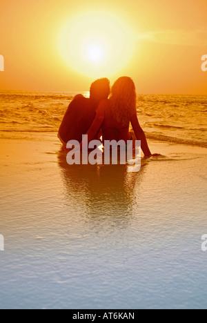 Couple assis à la plage, se découpant au coucher du soleil, aux Maldives Banque D'Images