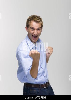 Jeune homme souriant de poing serré, portrait Banque D'Images