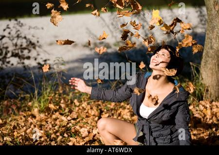 Germany, Bavaria, woman relevant les feuilles d'automne, portrait Banque D'Images