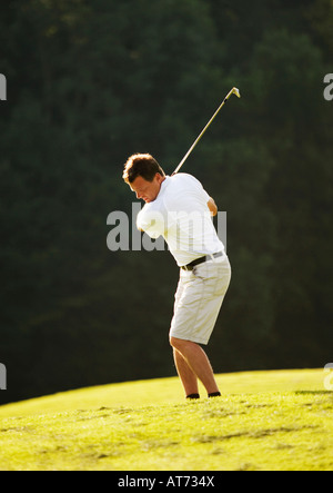 L'Autriche, Male golfer swinging club le fairway Banque D'Images