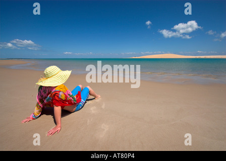 Attractive Woman sitting on beach wrap rouge Banque D'Images