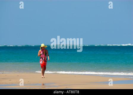 Jeune femme marchant sur la plage en paréo coloré. Banque D'Images