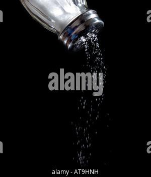 Salière avec du sel en provenance de sodium sel salé tomber venant fond noir aliments alimentaires Banque D'Images