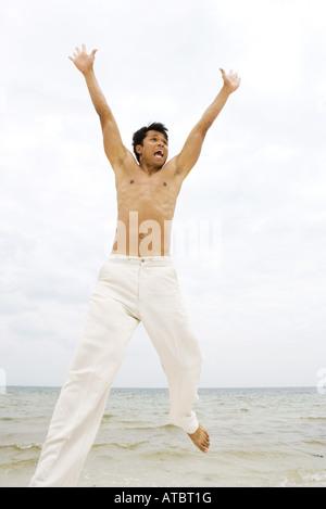Man dans l'air à la plage, bras levés, à l'écart Banque D'Images