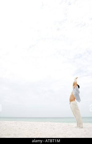 Homme debout dans sun salutation posent sur plage, vue latérale Banque D'Images