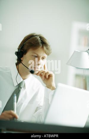 Businessman wearing headset, looking at laptop computer, la main sous le menton
