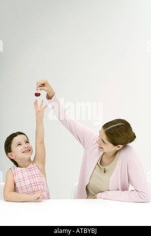 Mother holding up cerises, fille d'atteindre, à la fois smiling Banque D'Images