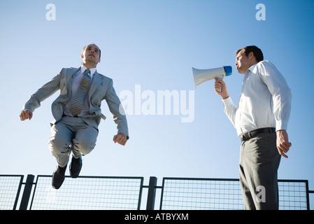 Businessman criant dans un mégaphone, collègue de sauter en l'air, low angle view Banque D'Images