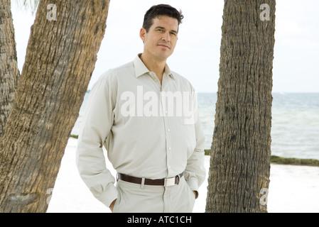 Homme debout entre les troncs des arbres, les mains dans les poches, looking at camera Banque D'Images