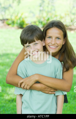 Adolescente et jeune frère smiling at camera, portrait