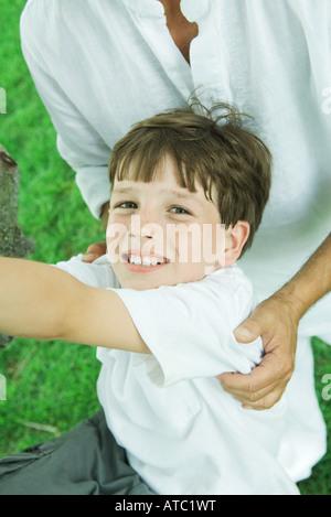Garçon avec ses mains sur ses épaules, smiling at camera, portrait Banque D'Images