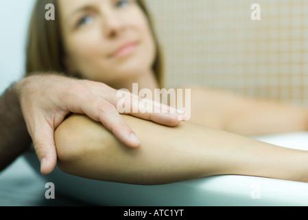 Femme dans une baignoire avec la main de l'homme sur son coude, l'accent sur le premier plan, Portrait Banque D'Images