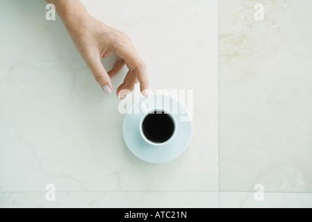 Hand Reaching for Coffee cup, vu à partir de juste au-dessus Banque D'Images
