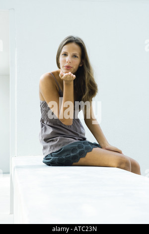 Teenage girl sitting, blowing kiss at camera Banque D'Images
