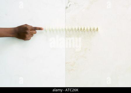 Enfant tendant vers la queue dominoes, cropped view of hand Banque D'Images