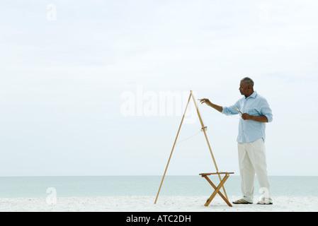 Senior man painting canvas sur la plage, vue latérale Banque D'Images
