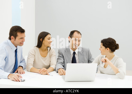 Groupe de partenaires d'affaires, hommes et femmes, assis à table avec un ordinateur portable, smiling Banque D'Images