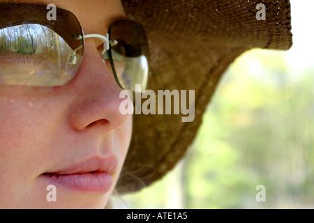 Femme portant des lunettes de soleil et chapeau de paille Banque D'Images
