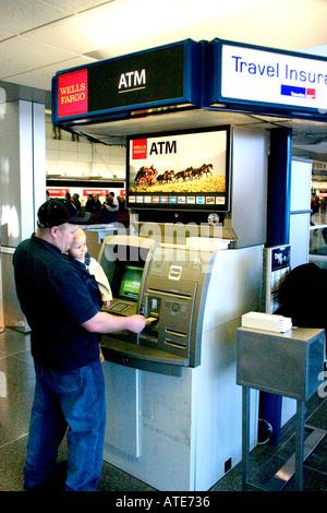 Père du retrait d'argent au distributeur de billets dans la région de Minneapolis-St. Paul International Airport. Banque D'Images