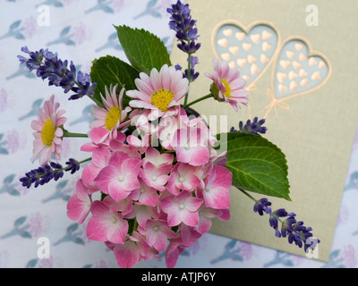 Message d'amour avec carte postale avec deux coeurs et petit bouquet bouquet de fleurs en rose Banque D'Images