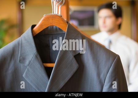 Close-up d'un costume d'affaires accrochée à un porte manteau avec un homme d'affaires dans l'arrière-plan Banque D'Images