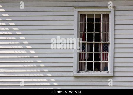 Deux drapeaux américains sur l'affichage dans la fenêtre de l'immeuble avec parement en bois blanc Banque D'Images