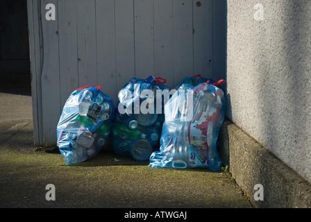 Sacs de recyclage bleu plein de bouteilles et boîtes en attente de pick up Banque D'Images