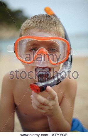 Jeune garçon sur la plage portant masque et tuba Banque D'Images