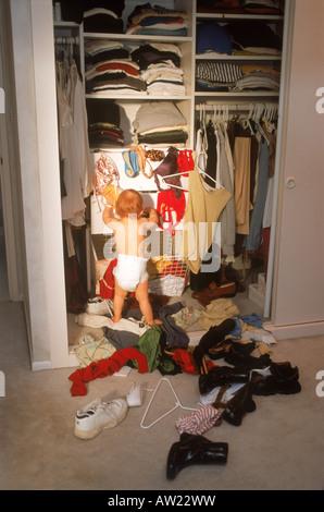 Bébé dans la chambre parents penderie Créer mess mixte de chaussures et vêtements Banque D'Images