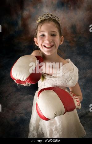 Jeune fille posant en robe avec de la terre et des gants de boxe Banque D'Images