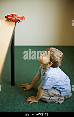 Le désir de l'enfant pour une voiture sport rouge quand il grandira Banque D'Images