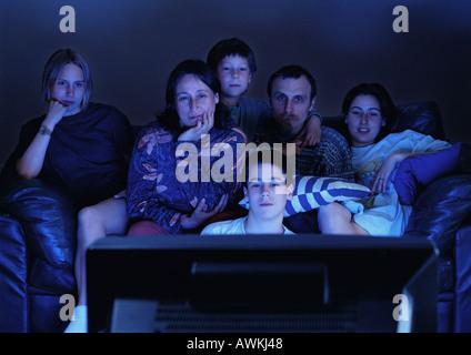 Famille regardent la télévision ensemble dans l'obscurité. Banque D'Images