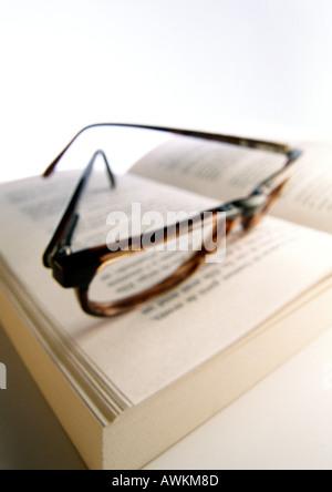 Portant des lunettes à livre ouvert, close-up Banque D'Images