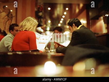 Groupe de jeunes gens assis dans les menus de restaurant Banque D'Images