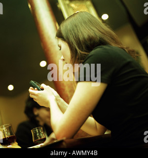 Jeune femme assise, dialing cell phone, low angle view Banque D'Images