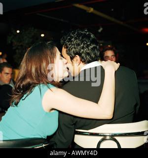 Jeune femme jeune homme embrassant sur la joue en bar, vue arrière Banque D'Images