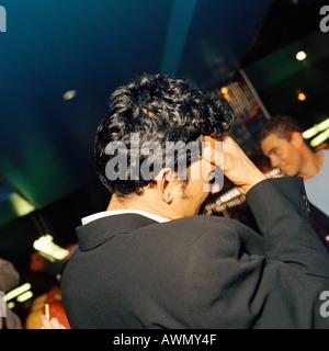 Jeune homme tenant tête en bar, vue arrière. Banque D'Images