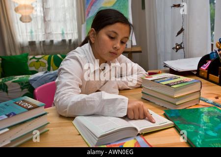 Jeune écolière faire leurs devoirs en pépinière, reading book Banque D'Images