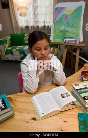 Jeune écolière faire leurs devoirs en pépinière, livre de lecture et en contemplant Banque D'Images