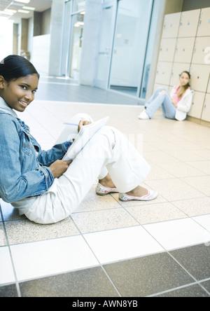 Les filles de l'adolescence assis sur le plancher du couloir de l'école