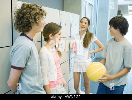 Groupe de jeunes adolescents se tenant ensemble près des casiers de l'école Banque D'Images