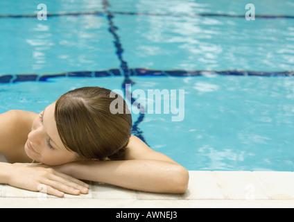 Young woman resting head sur le côté de la piscine Banque D'Images