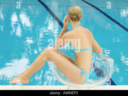 Woman in bikini sitting by pool en fauteuil transparent Banque D'Images