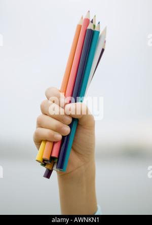 Enfant's hand holding poignée de crayons de couleur Banque D'Images