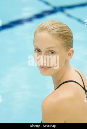 Femme par pool, looking over Shoulder, smiling at camera Banque D'Images