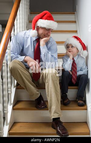 Un père et son fils s'ennuyer assis sur des escaliers Banque D'Images