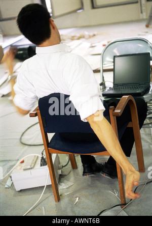 Man sitting in chair s'étendant les bras, en face de l'ordinateur portable sur une chaise Banque D'Images
